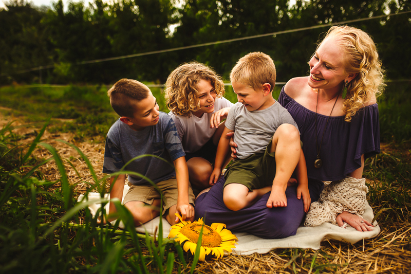 Family & Maternity Photographer, a mom sits in the grass on a blanket with her three boys admiring them