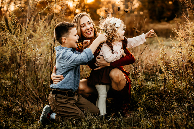 Family & Maternity Photographer, a mother holds her gtwo toddlers close as they reach for tall dry grass