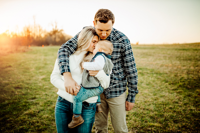 Family & Maternity Photographer, Mom and dad embrace in a grassy field as they hold and kiss their toddler son