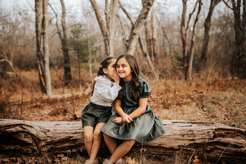 Family & Maternity Photographer, two little girls sit on a log in the forest, one whispers into the other's ear, the other girl smils