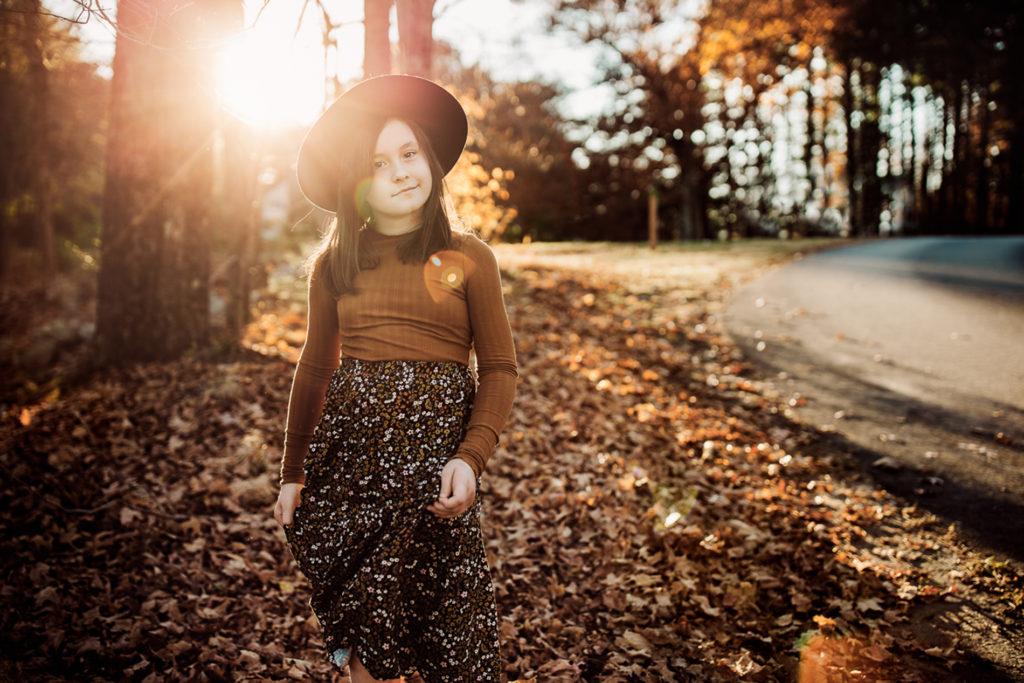 Family & Maternity Photographer, a girl walks through the fall leaves on a windy road